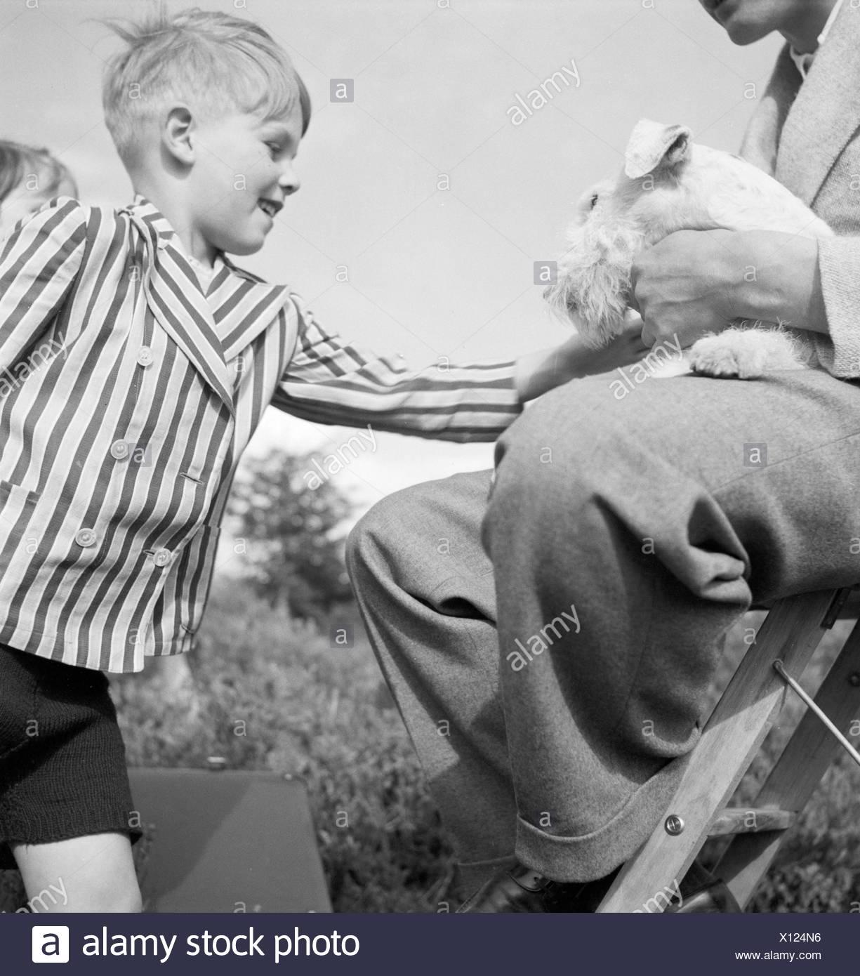 Ein Kleiner Junge Streichelt Einen Foxterrier, 1930er Jahre Deutschland. Ein kleiner Junge mit einem Fox Terrier, Deutschland der 1930er Jahre. Stockbild