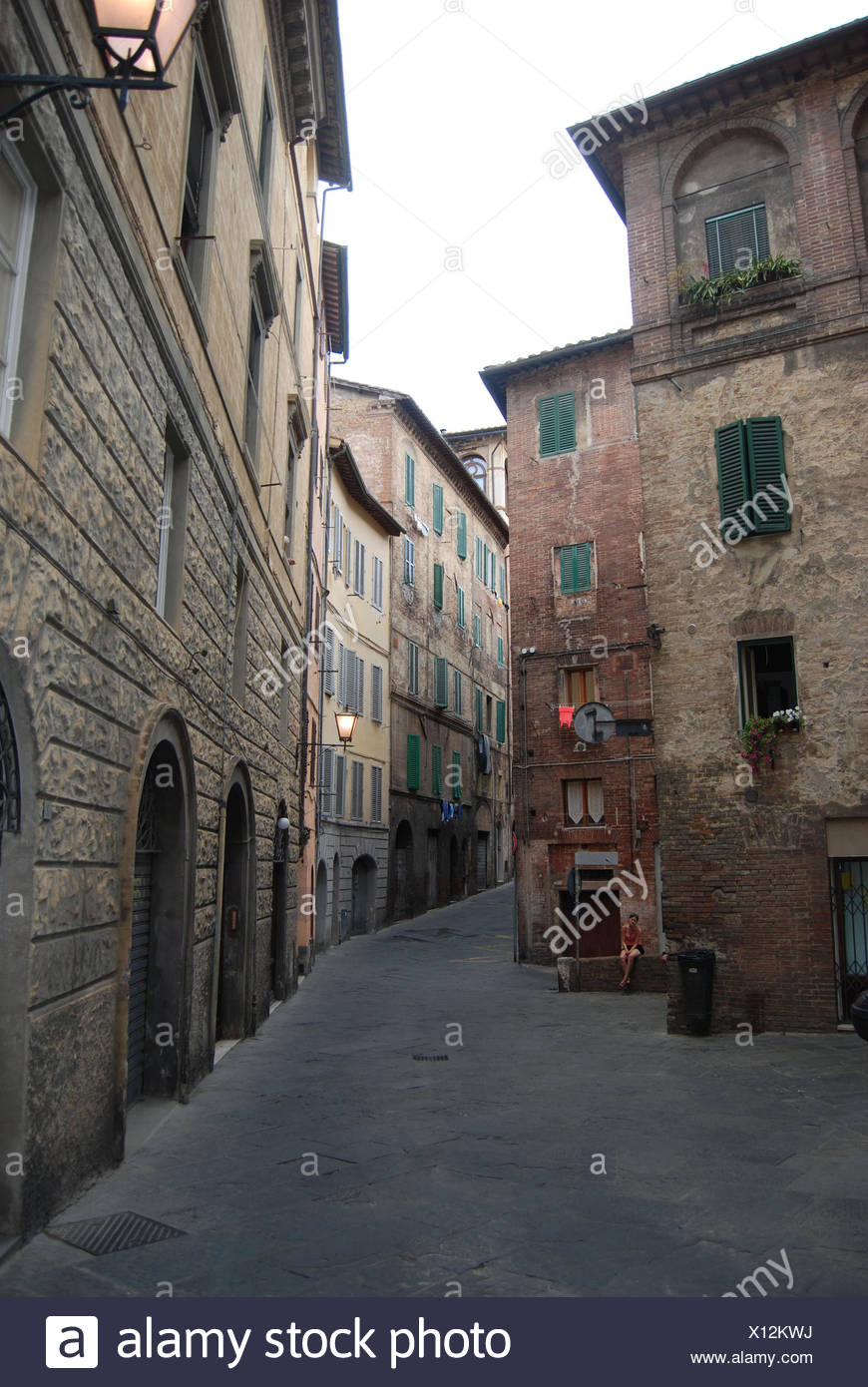 Jugendliche Frau Sitzt Alleine Auf Einer Mauer Mit Gekreuzten Beinen in Einer Gasse in der Altstadt von Siena, Toskana, Italien Stockbild