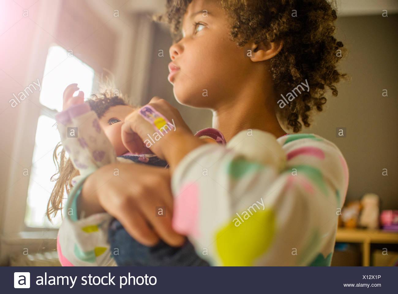 Nahaufnahme von Mädchen tragen und Fütterung Puppe Stockbild