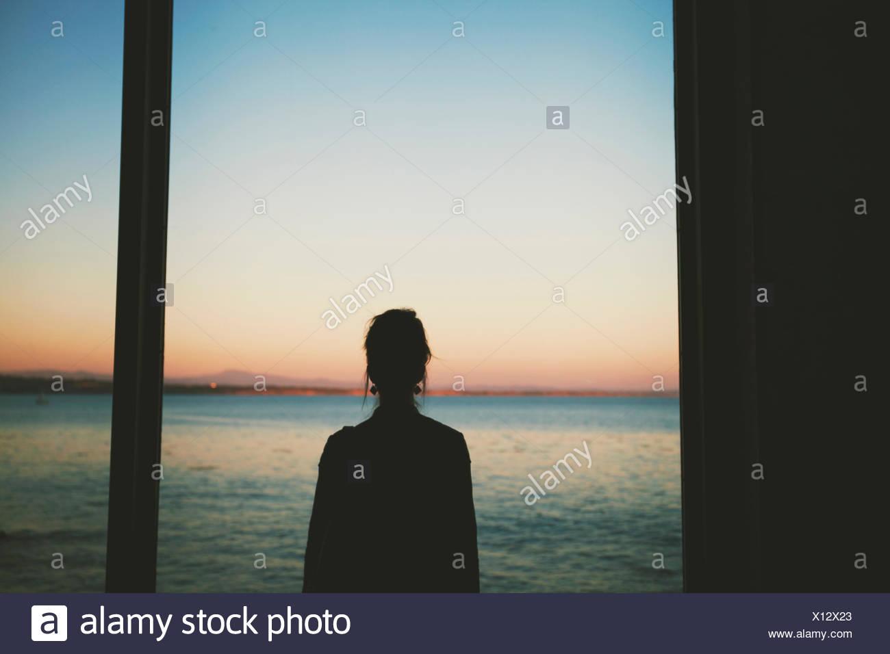 Frau, die auf hoher See durch Fenster Stockbild