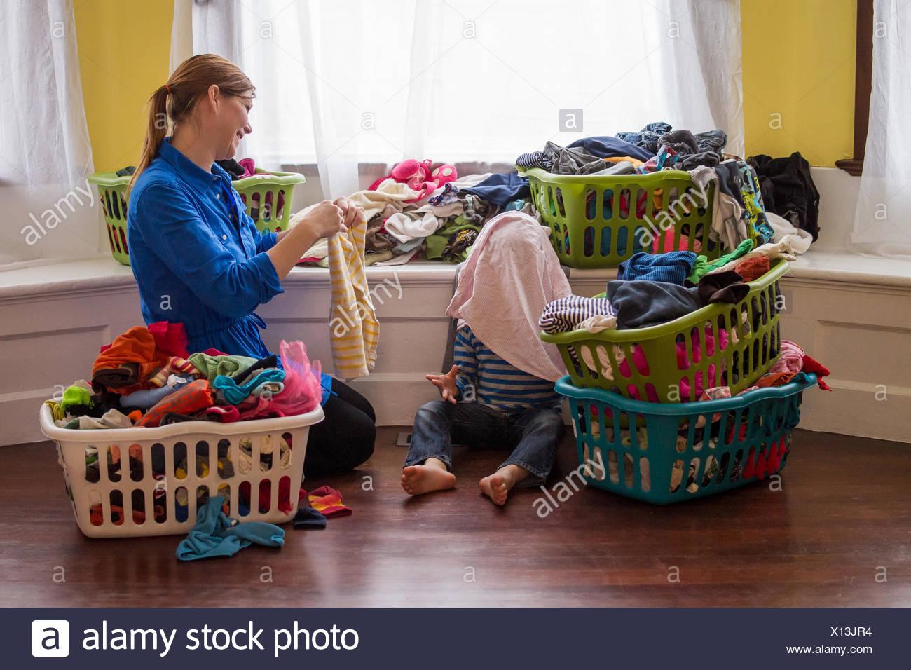 Mutter und junge Falten Kleidung und lachen zusammen Stockbild
