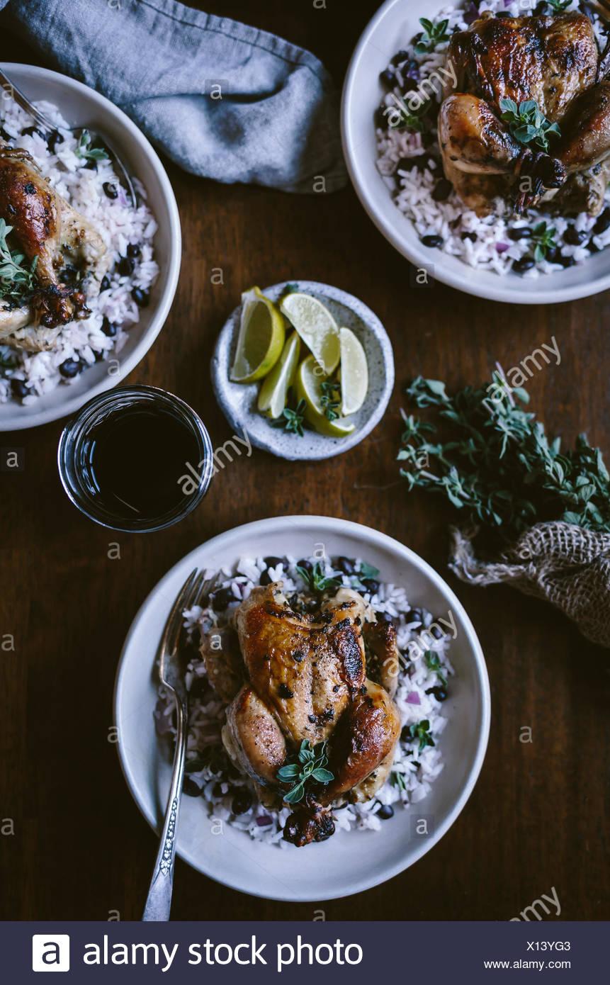 3 Platten mit kubanischen gerösteten Spiel Hennen über schwarze Bohnen Reis serviert werden aus der Ansicht von oben fotografiert. Stockbild