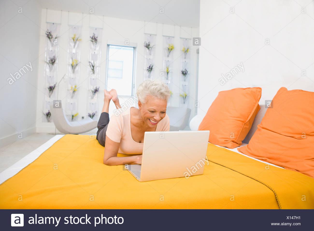 Frau mit Laptop am Bett Stockbild