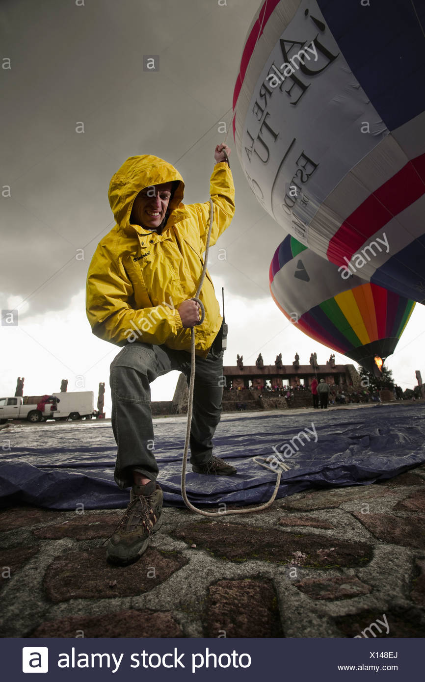 ein Mann zieht einen Ballon, während es, im Centro Ceremonial Otomi, Estado de México, Mexiko aufgeblasen ist. Stockbild