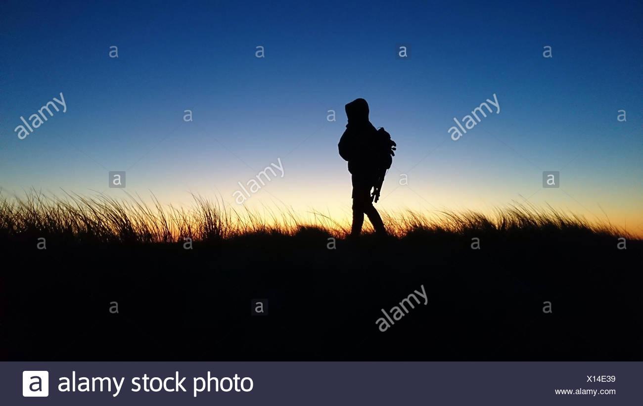 Silhouette der Mann zu Fuß in ländlichen Landschaft bei Sonnenuntergang, Dänemark Stockbild