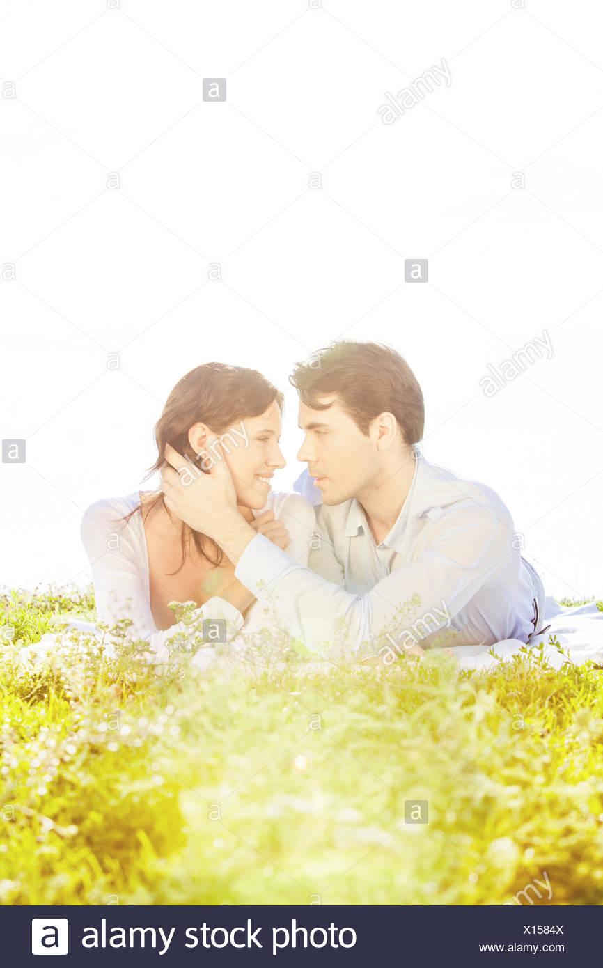 Liebevoller Mann Frau beim Betrachten sie auf Rasen gegen klaren Himmel berühren Stockfoto