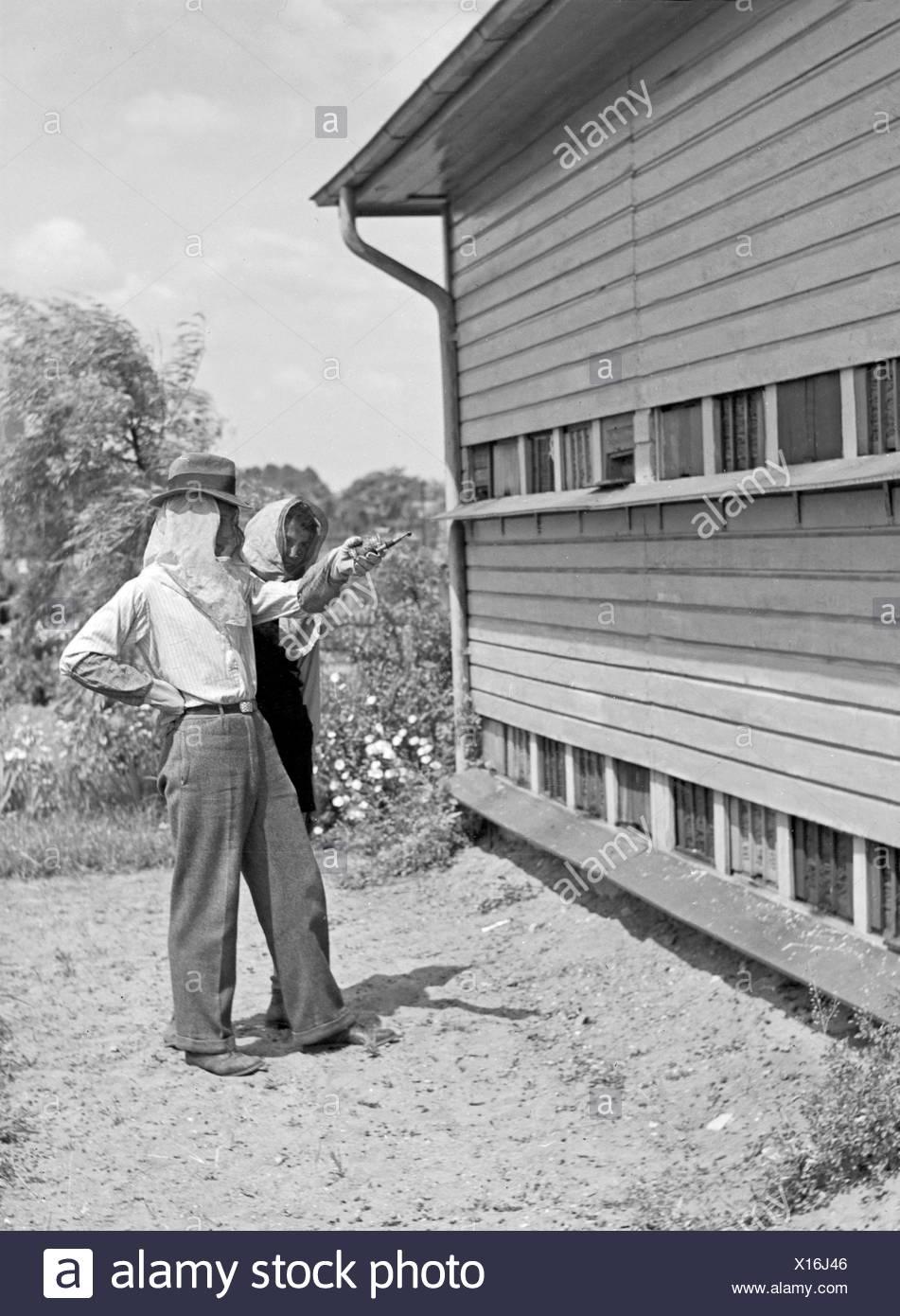 Zwei Imker Stehen in Schutzkleidung Vor Dachmarke Bienenstock, 1930er Jahre Deutschland. Zwei Imker in Protectitve Kleidung stand vor einem Bienenstock, Deutschland der 1930er Jahre. Stockbild