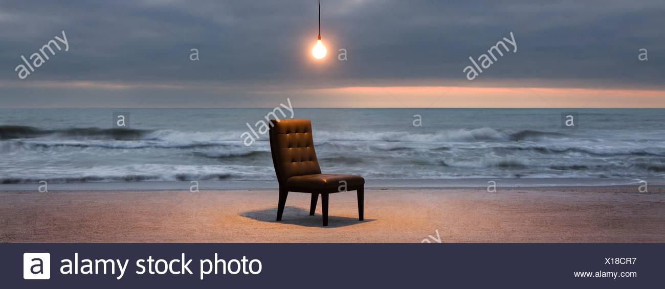 Glühbirne leuchtet über Stuhl am Strand bei Sonnenuntergang Stockbild