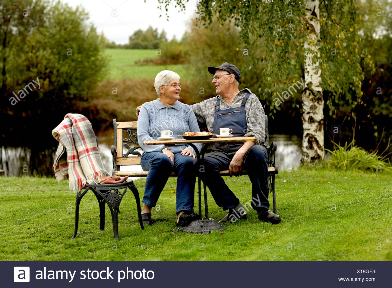 Senior paar sitzt am Tisch im Hinterhof Stockbild