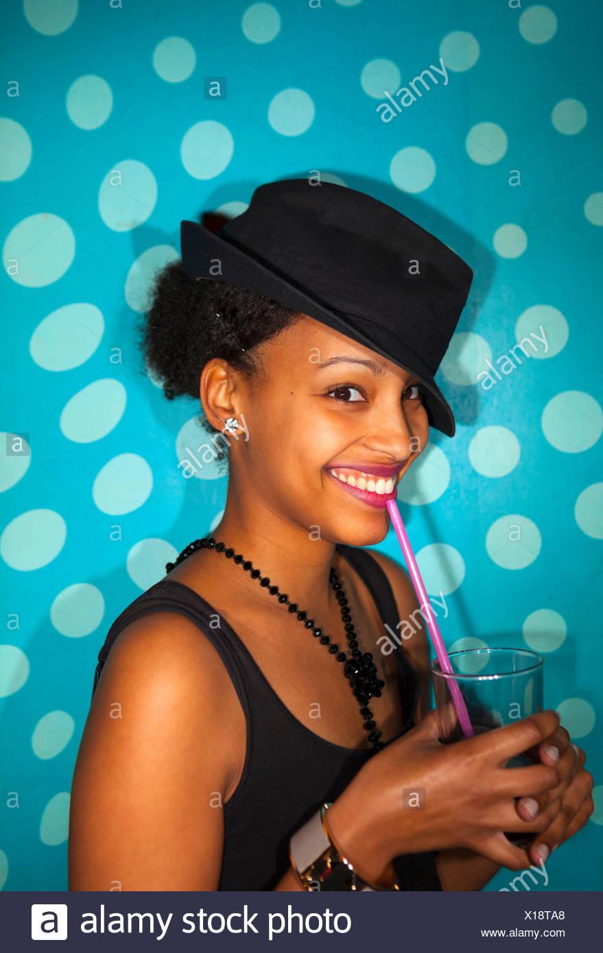 Portrait von junge Frau mit gemischter Herkunft Ethnie lächelnd und halten Trinkglas mit Stroh Stockbild