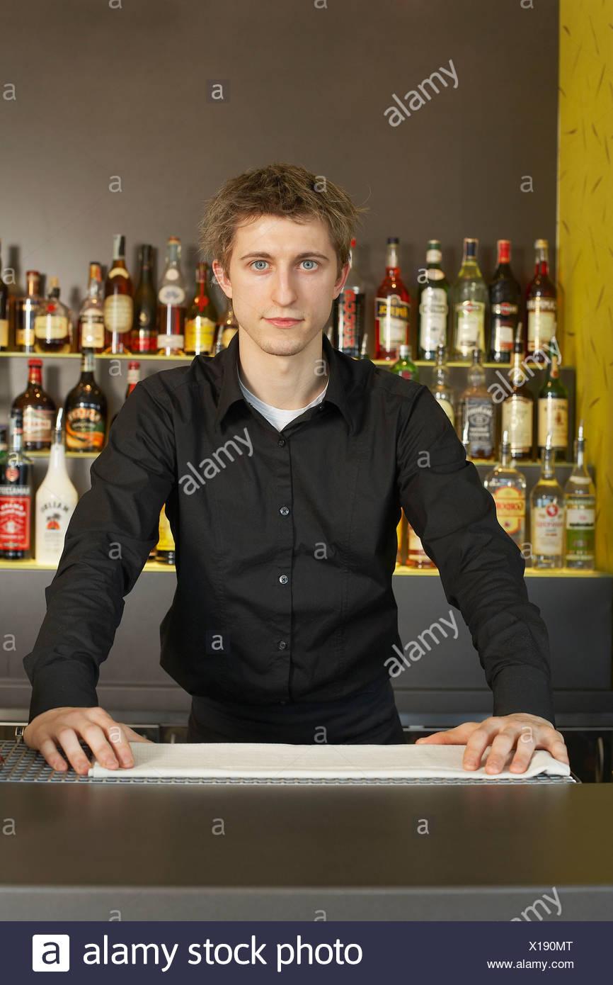 Porträt des jungen Barmann hinter seiner bar Stockbild