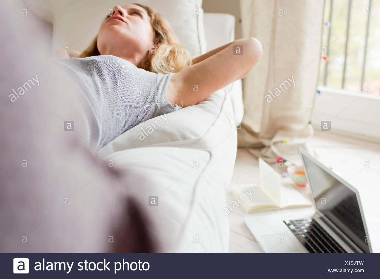 Frau liegt auf dem Sofa Tagträumen Stockbild