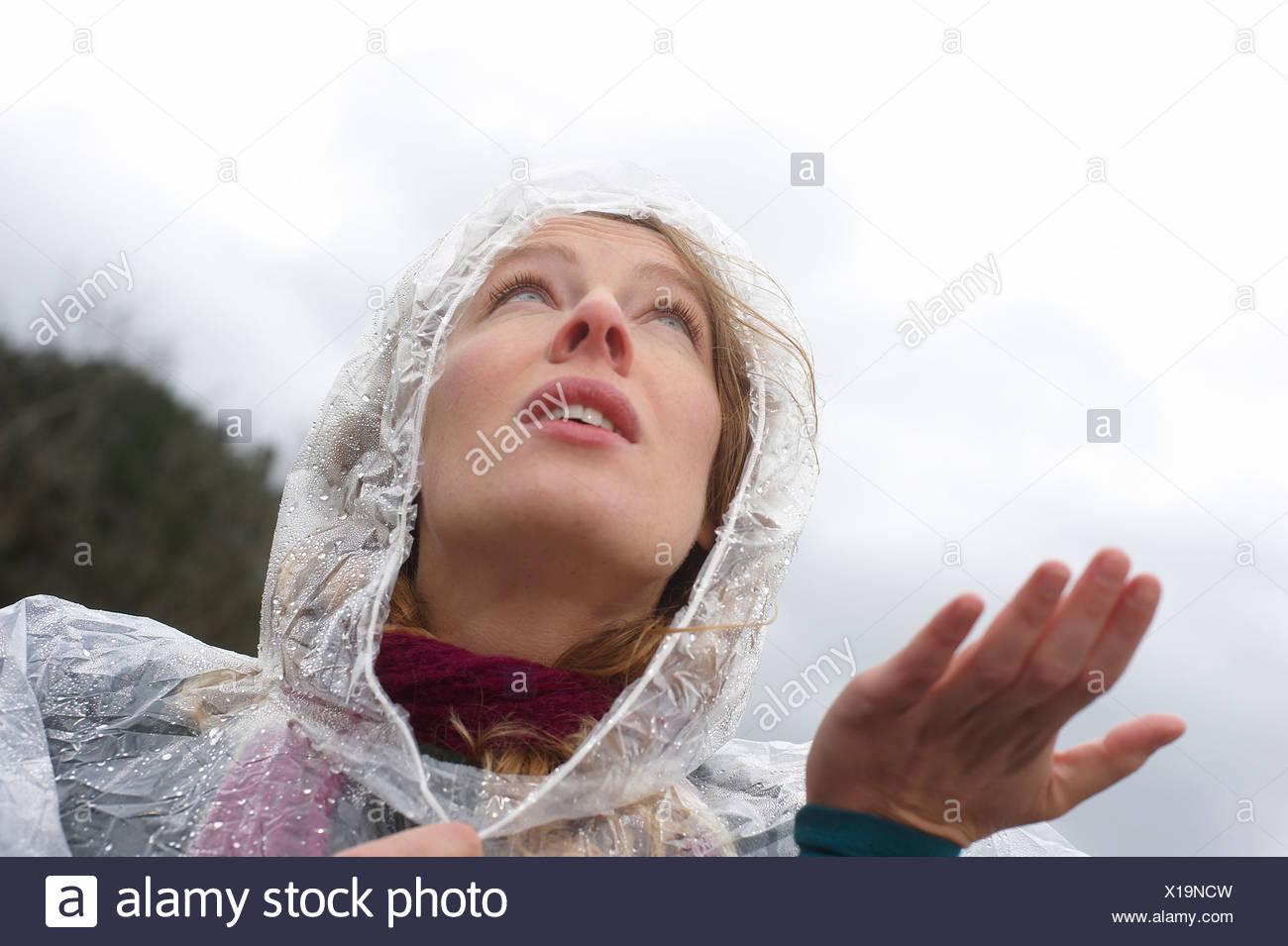 Eine Frau im Regen tragen einen Plastiken-Regenmantel Stockbild