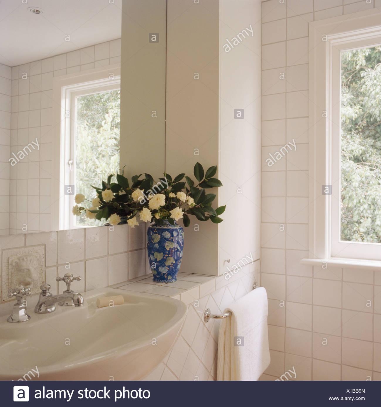 Cremefarbene Blüten und Grün lässt in blaue + weiße Vase auf ...