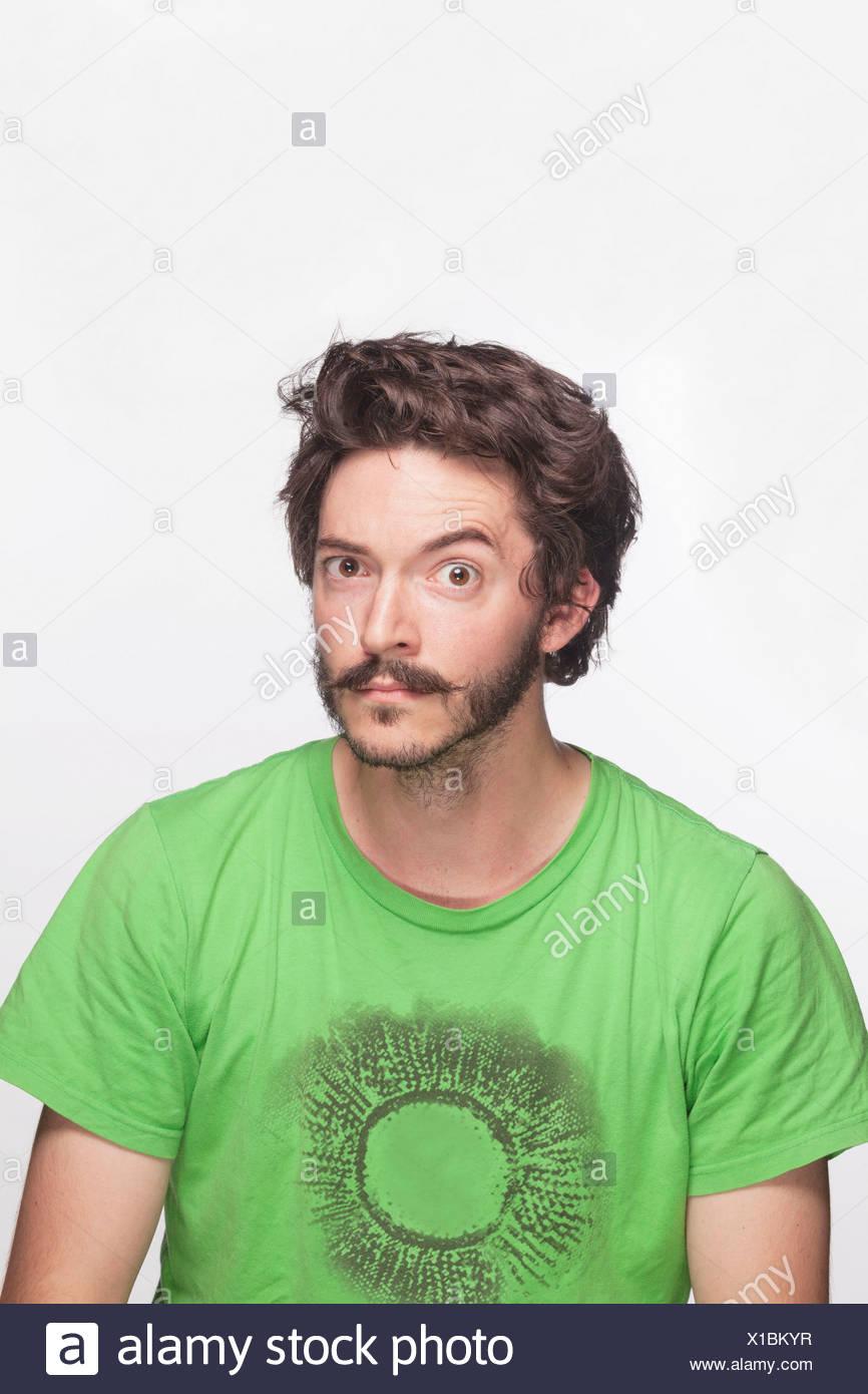 Junger Mann mit Augenbraue hob Blick in die Kamera, Studio gedreht Stockfoto
