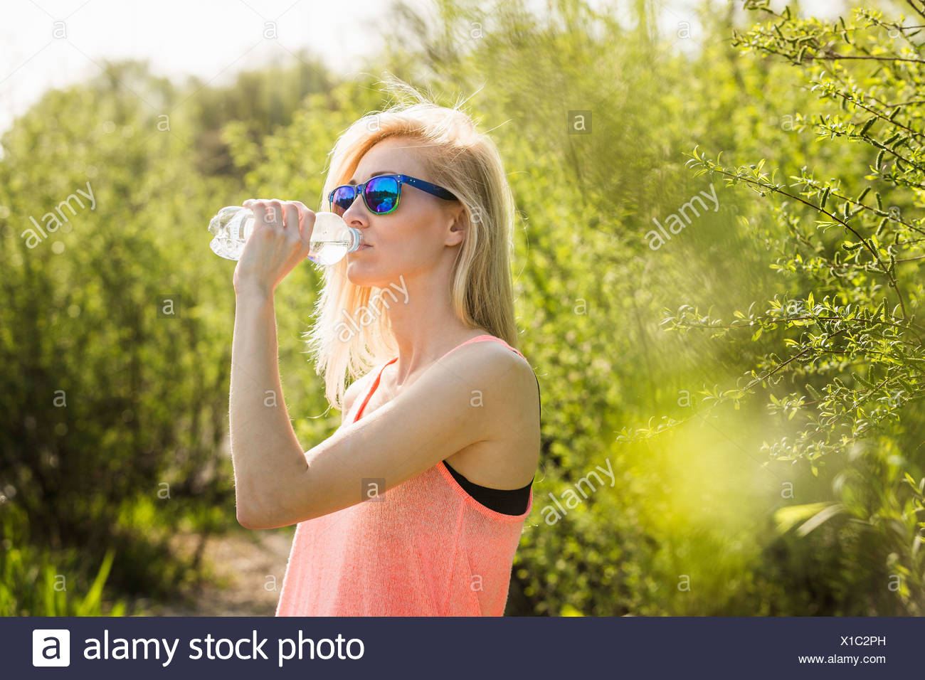 Junge Frau im Park, die Flasche Wasser trinken Stockbild