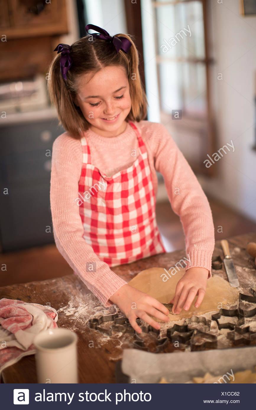 Mädchen schneiden Formen im Teig, hausgemachte Kekse zu machen Stockbild