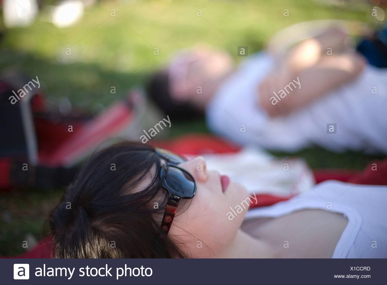 Eine junge Frau in einem Park liegend Stockbild
