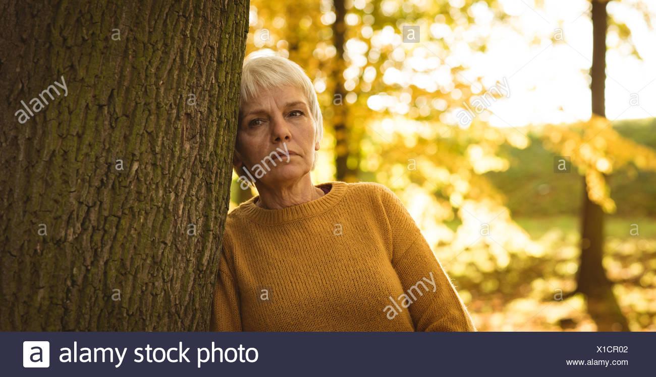 Nachdenklich senior Frau lehnte sich auf Baum im Park Stockbild