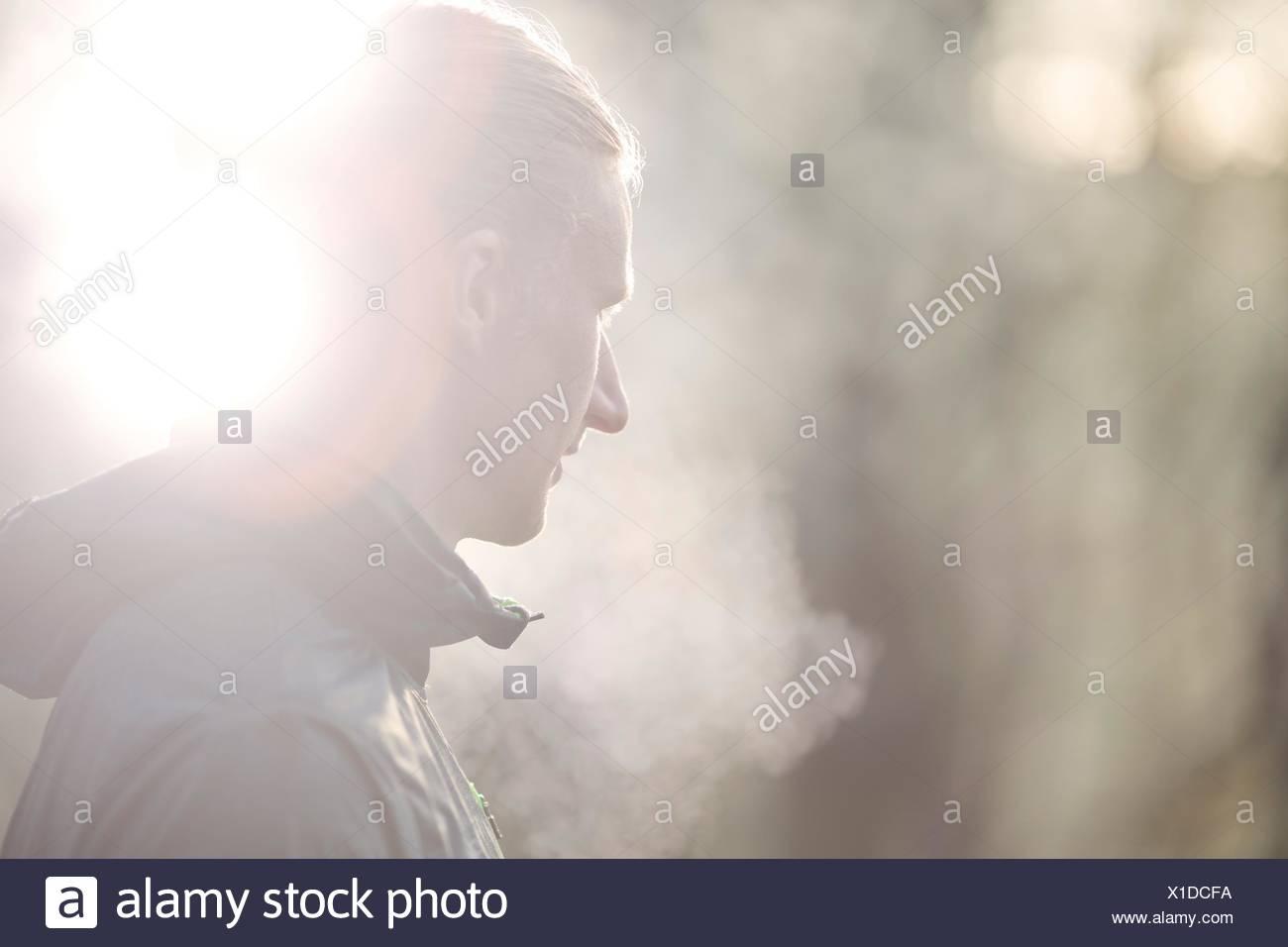 Seitenansicht der Mitte erwachsener Mann wegsehen, Kondensation von Atem Stockbild