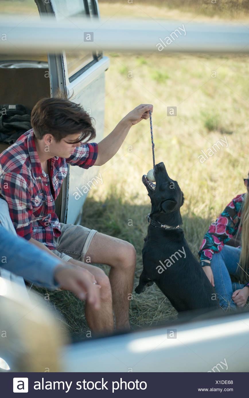 Junger Mann mit Hund spielen Stockbild