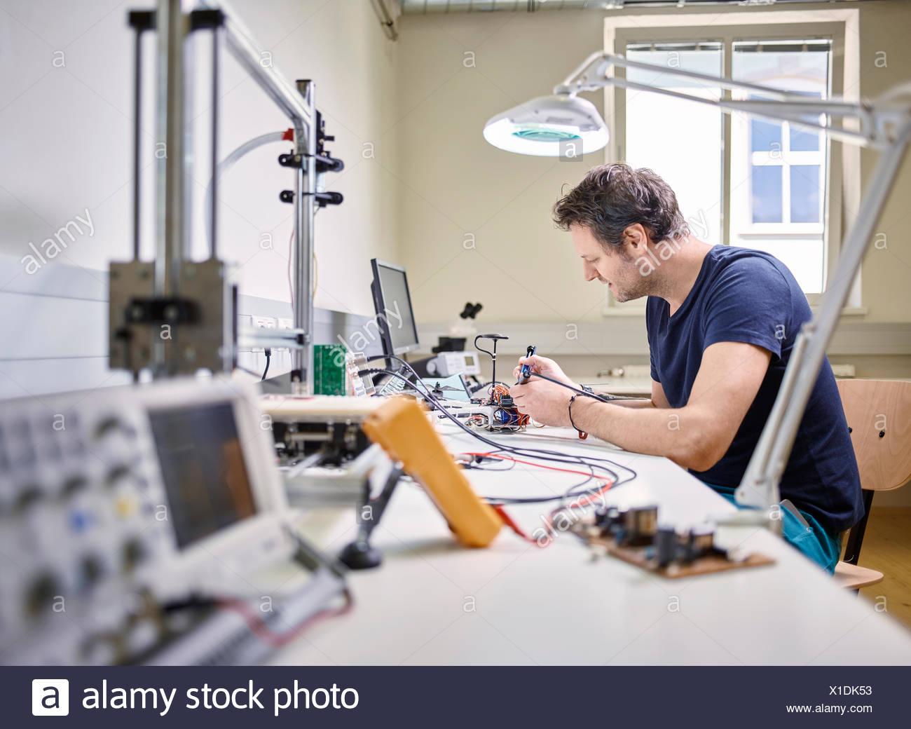 Mann im Elektroniklabor Löten Stockbild