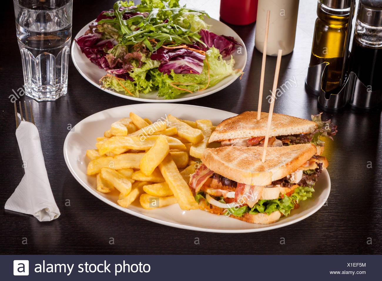 Clubsandwich Auf Getoastetem Weißbrot Mit Speck Und Pommes Frittes Straßenbildes Auf Einem Teller Stockbild