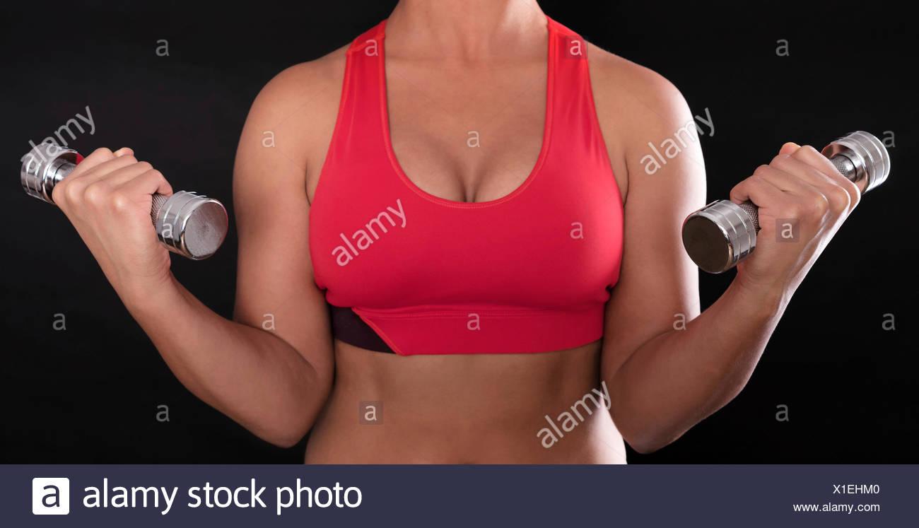 Junge Frau Oberkörper tragen einen roten Sport-BH dabei Fitnesstraining mit Chrom-Hanteln Stockbild