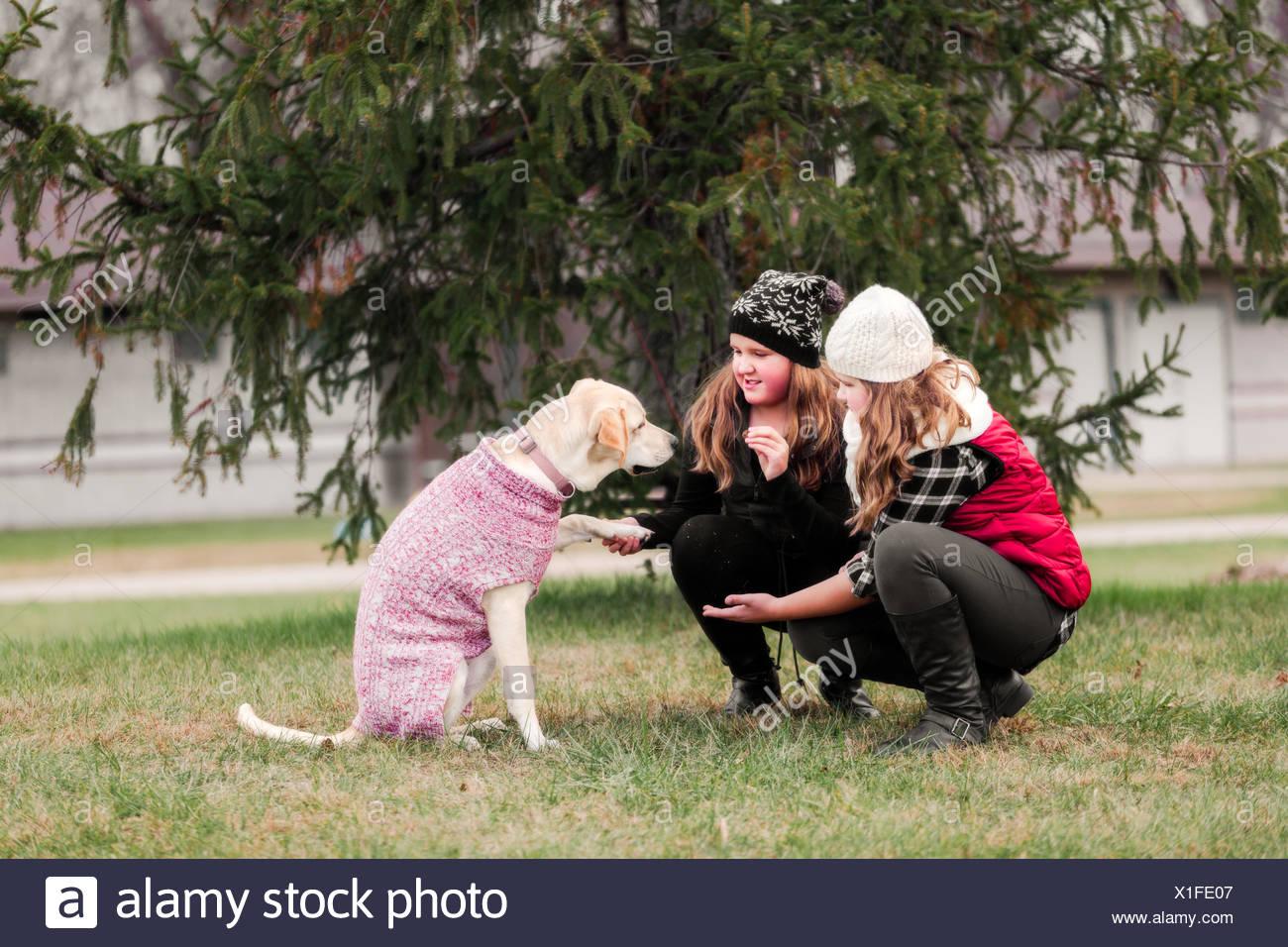 Mädchen Und Ihre Schwester Crouching Hund Die Pfote In Garten Zu