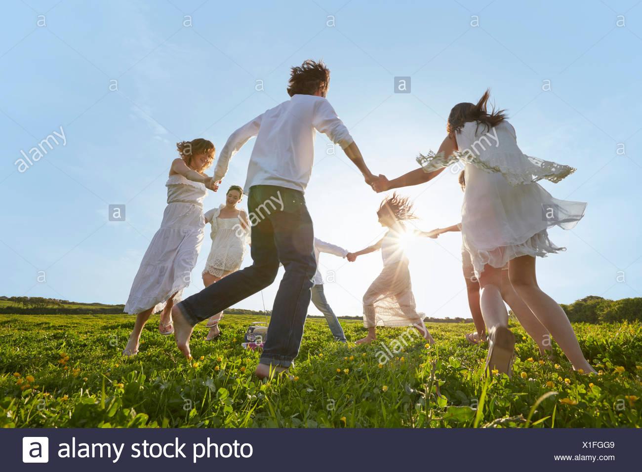 Gruppe von jungen Erwachsenen Freunden spielen Ring-a-Rosie im Feld Stockbild