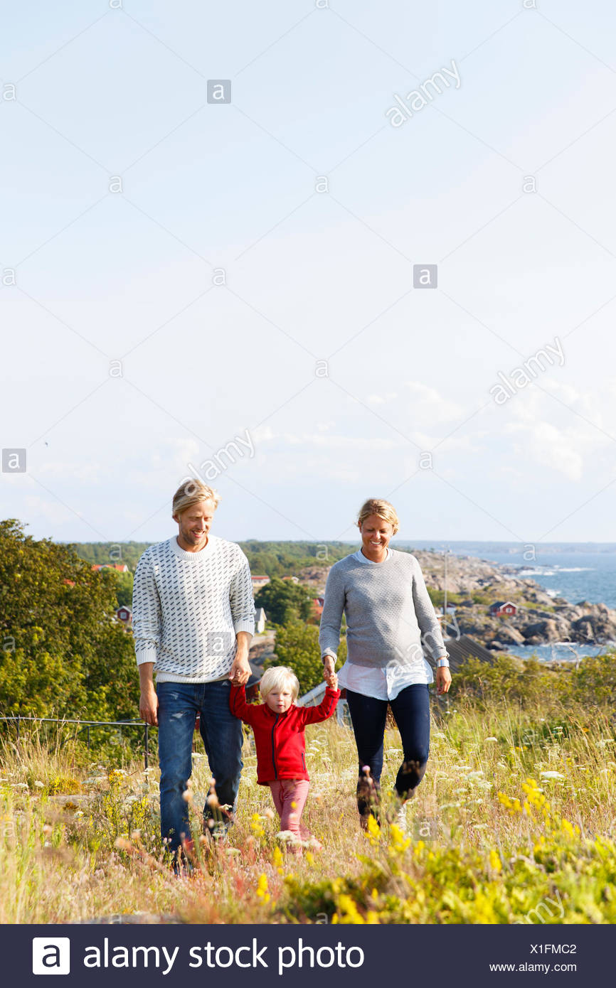 Schweden, Stockholmer Schären, Sodermanland, Oja, Frau und Mann zu Fuß mit Sohn (2-3) durch Wiese mit Meer im Hintergrund Stockfoto