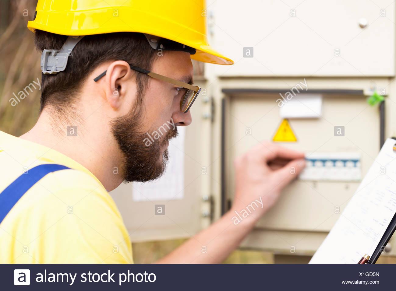 Elektriker überprüfen Sicherungskasten Stockbild