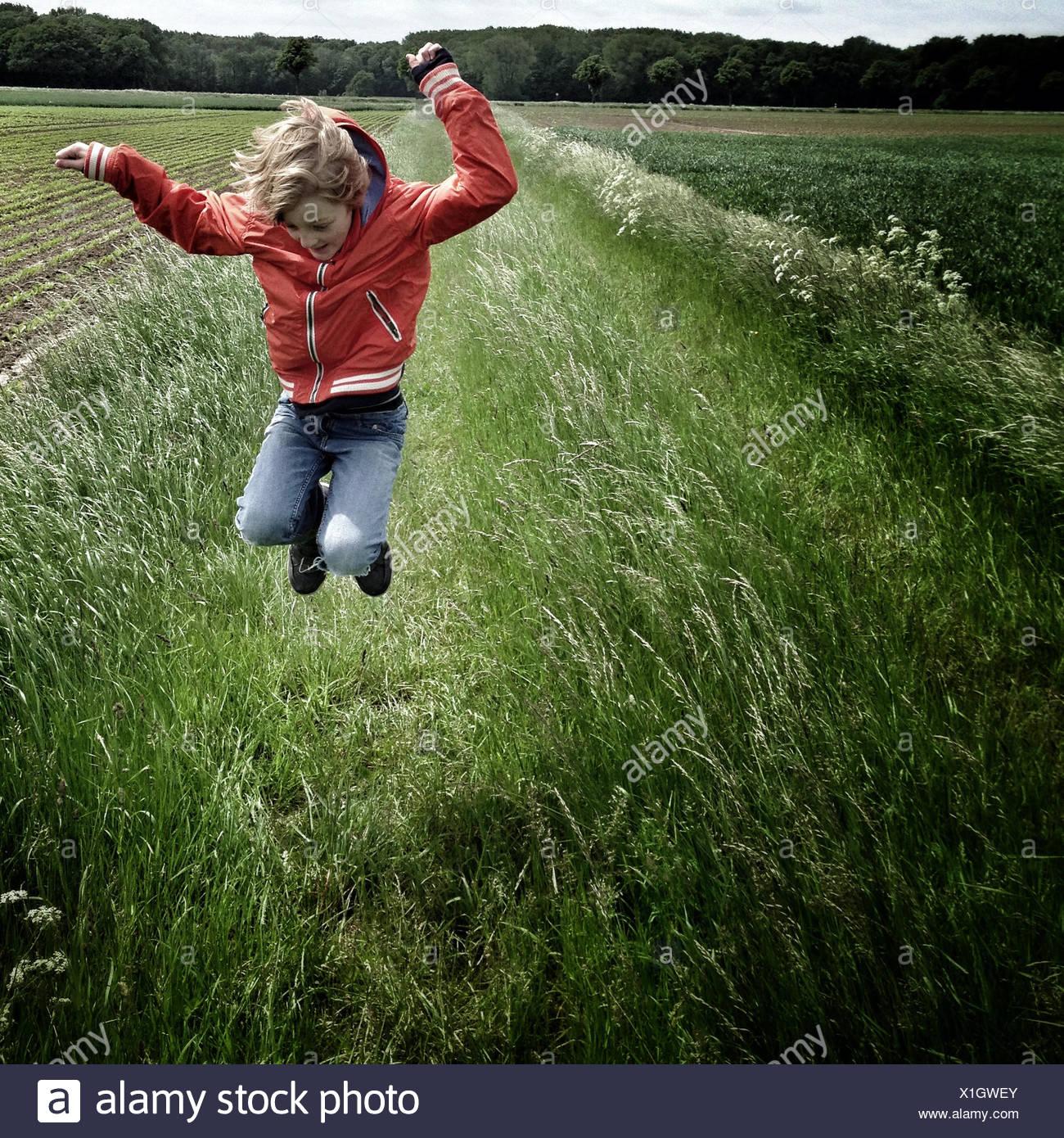 Junge springt In einem Feld Stockbild