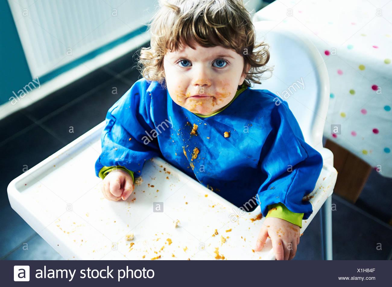 Schmutzige Mädchen Essen im Hochstuhl Stockbild