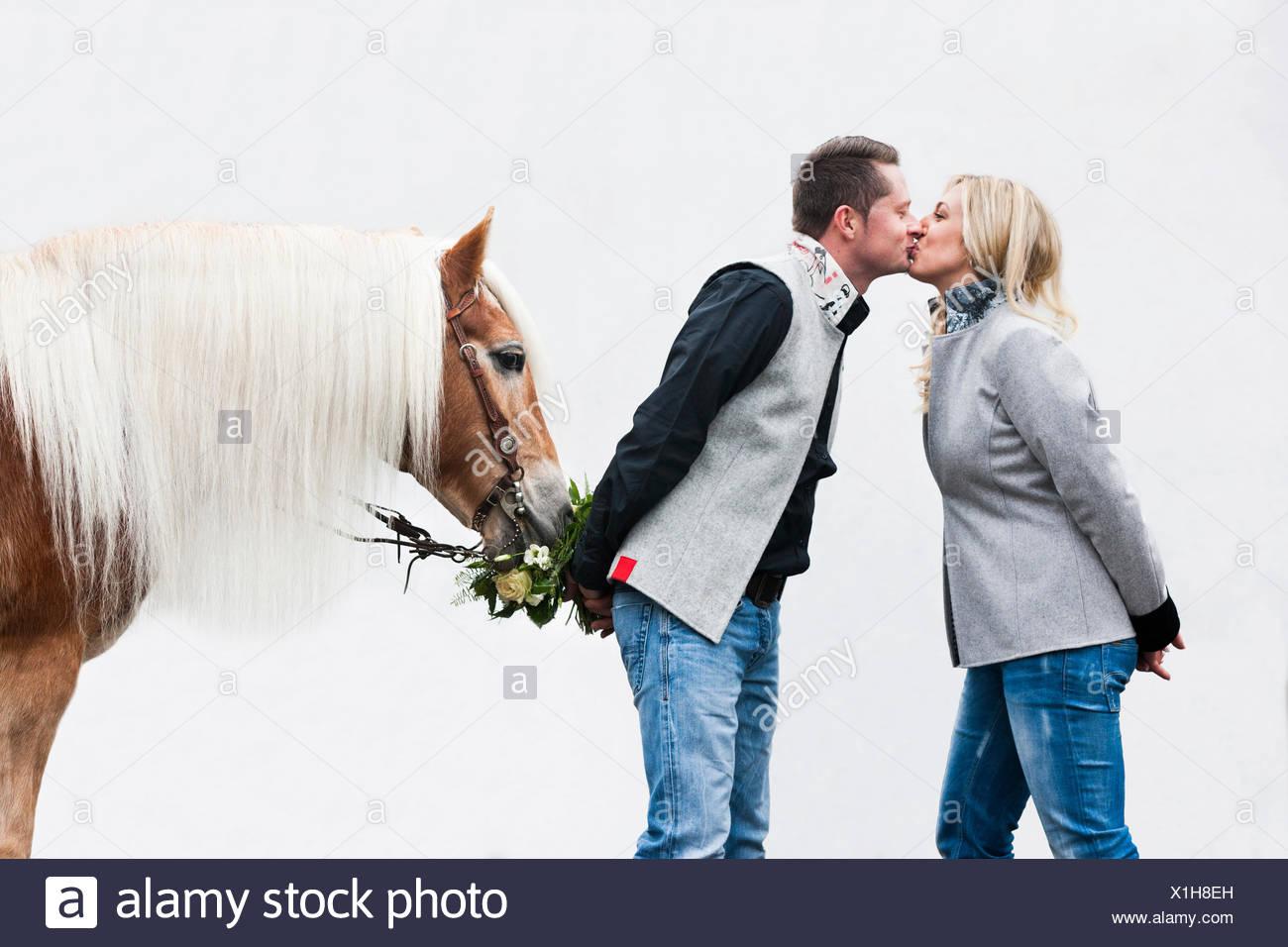 Mann und Frau küssen, Tyrolean Haflinger Essen Blumen, Nord-Tirol, Österreich Stockbild