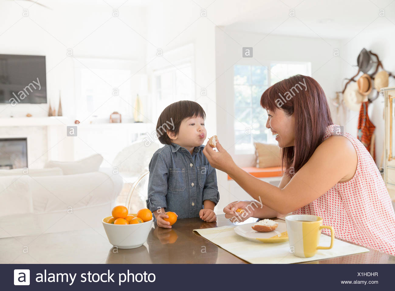 Mutter Fütterung Sohn am Esstisch Stockbild