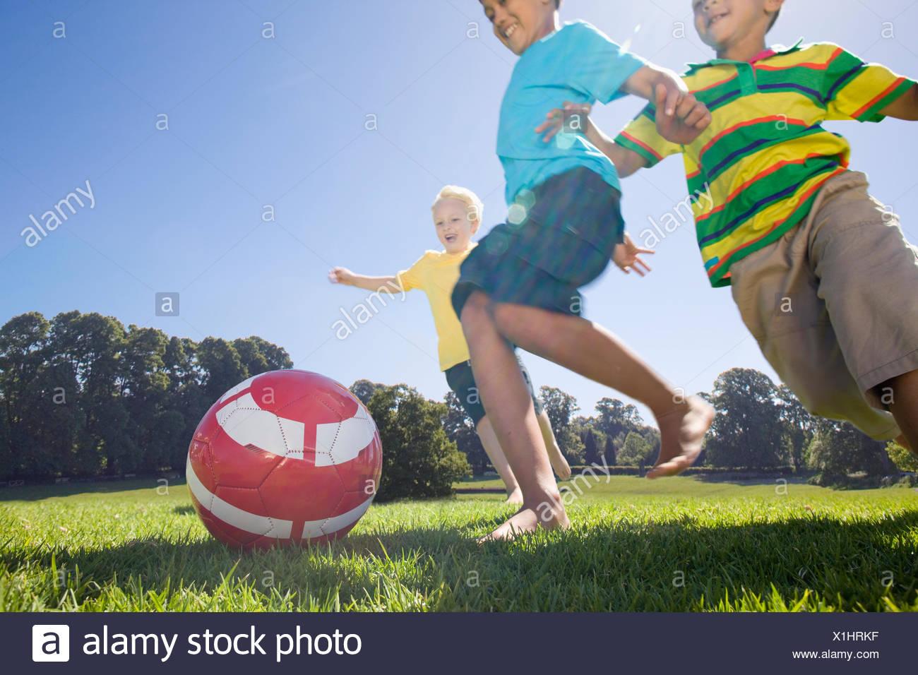 Lächelnden jungen spielen Fußball im park Stockbild
