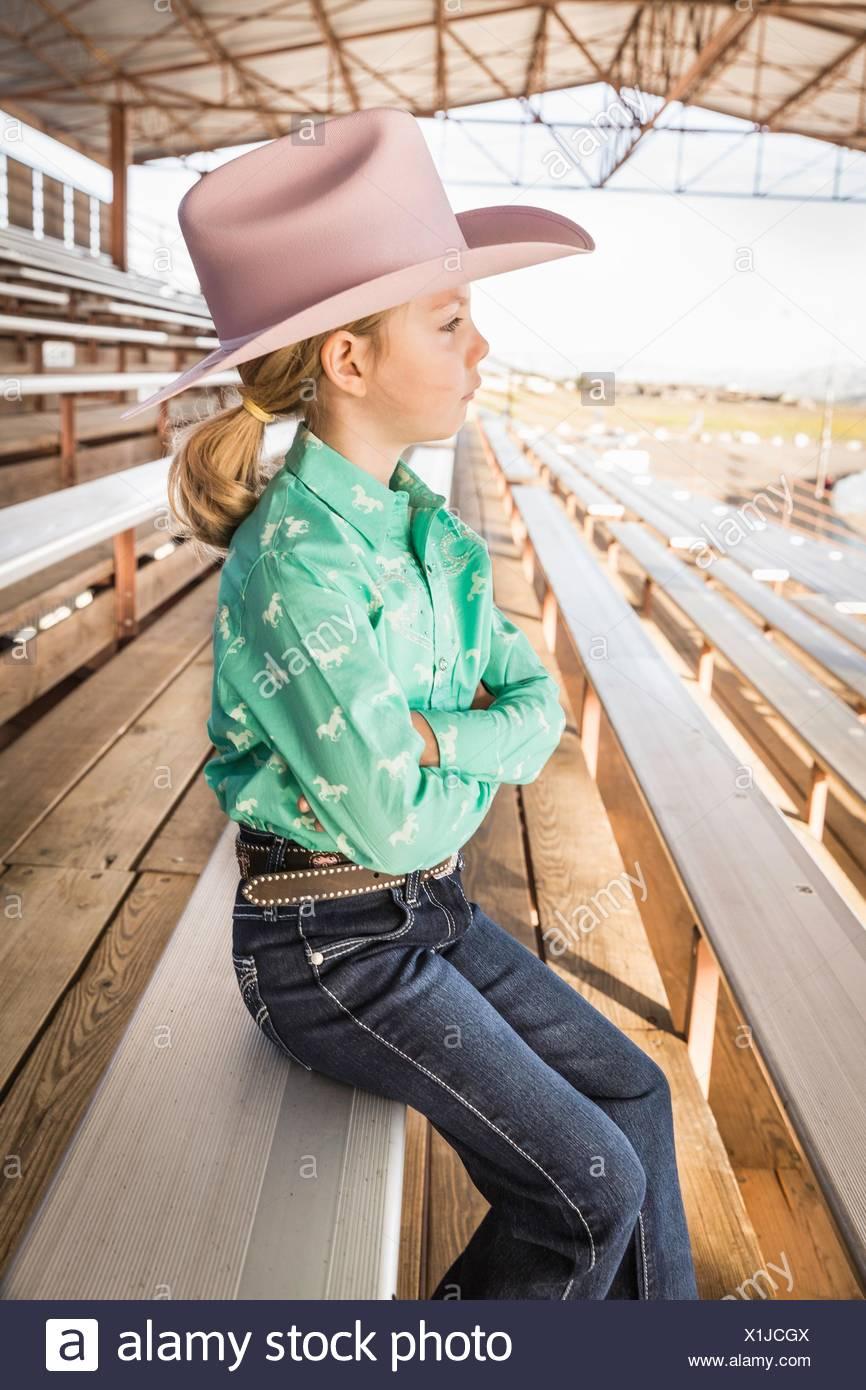 Mädchen tragen Cowboyhut auf Bank mit Armen gefaltet, Porträt Stockbild