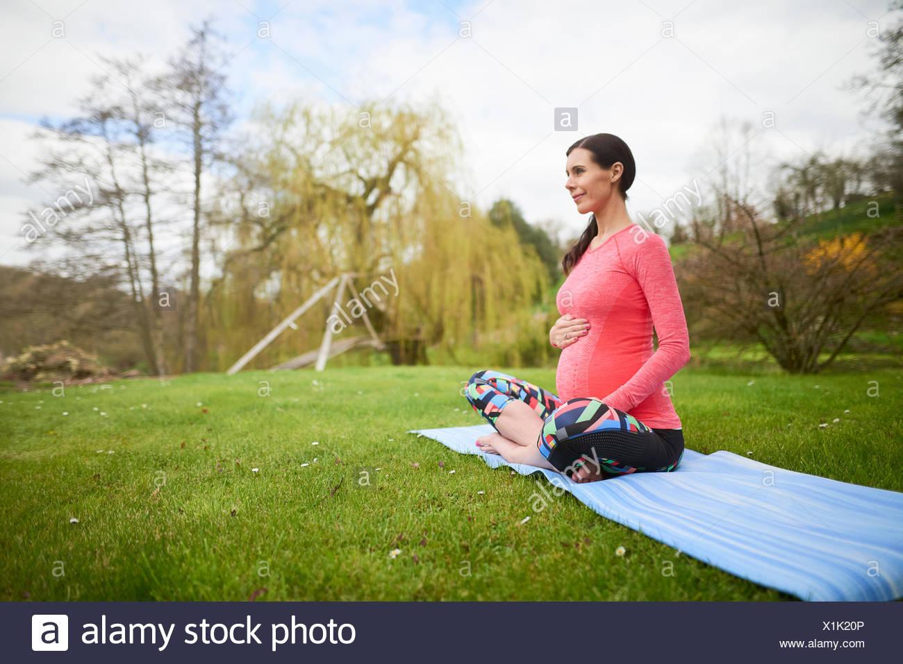 Schwangere Frau sitzen im Freien, halten Bauch Stockfoto