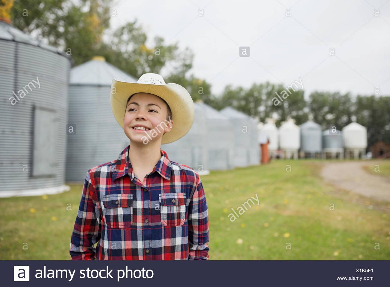 Junge in Cowboy-Hut lächelnd auf Bauernhof Stockbild
