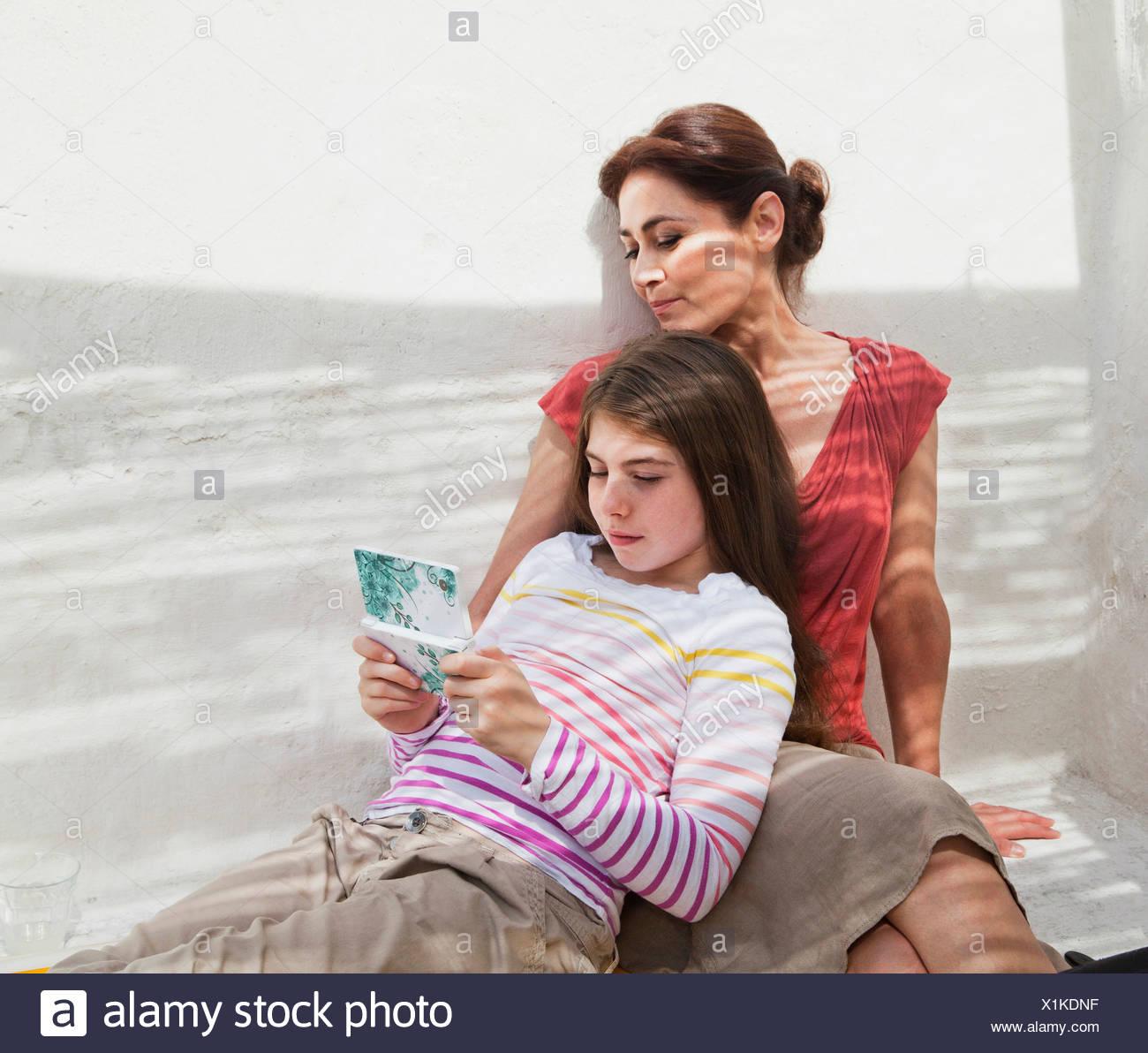Mutter und Tochter mit Hand gehalten Gerät Stockbild