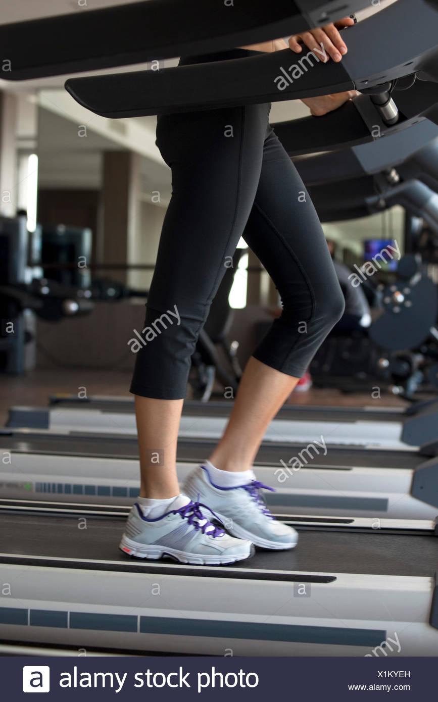 Frau auf Laufband im Fitnessstudio Stockbild