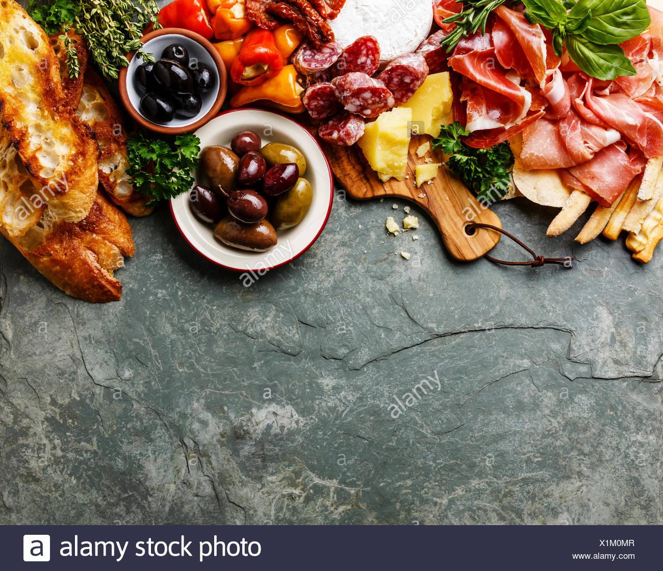 Italienische Küche Zutaten Hintergrund mit Schinken, Salami, Parmesan, Oliven, Brot klebt auf Stein Schiefer Stockbild