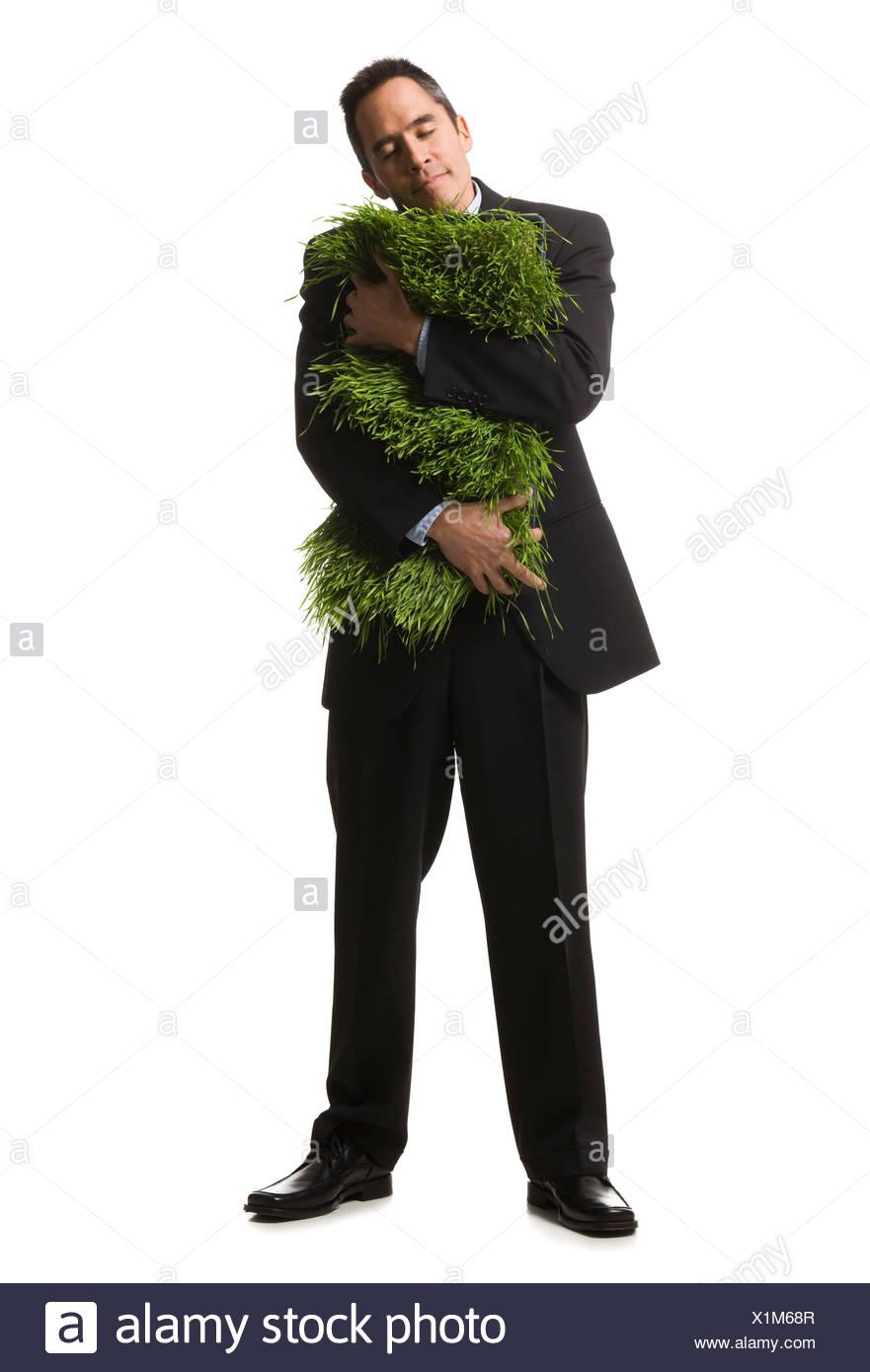 Unternehmer, die halten eines Patches Gras Stockbild