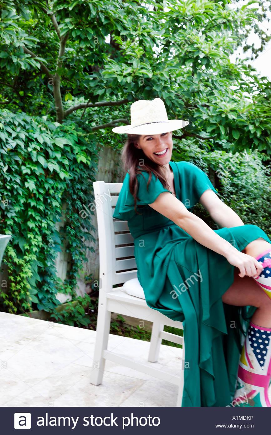 Junge Frau trägt grünes Kleid und Hut, auf Stuhl im Garten sitzend Stockbild
