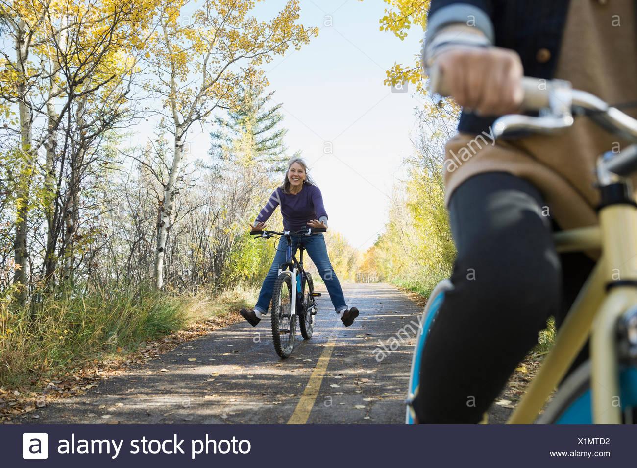Unbeschwerte Frau Reiten Fahrrad mit gespreizten Beinen Stockbild