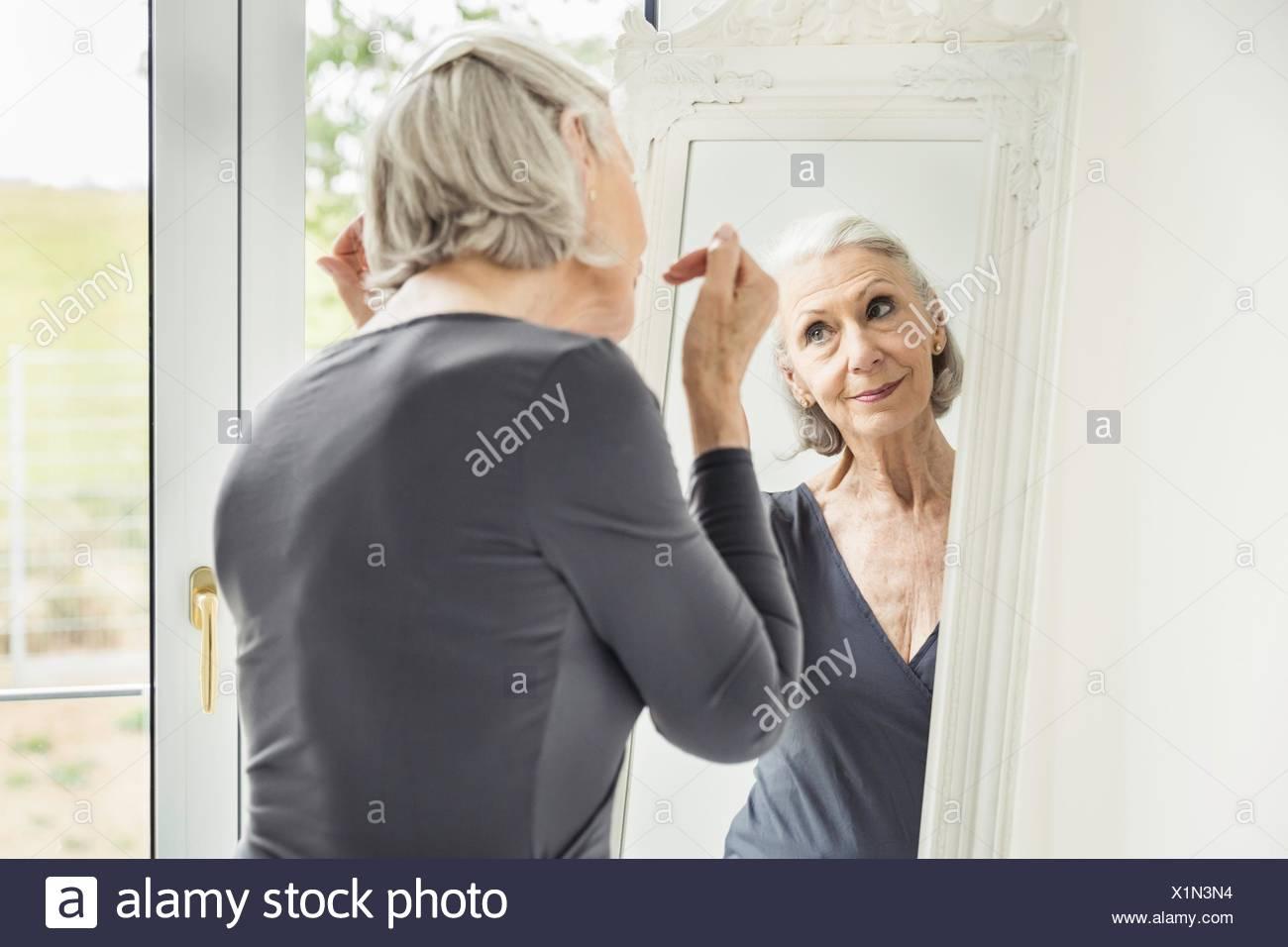 Grauen Haaren senior Frau bereitet sich selbst im Spiegel Stockbild