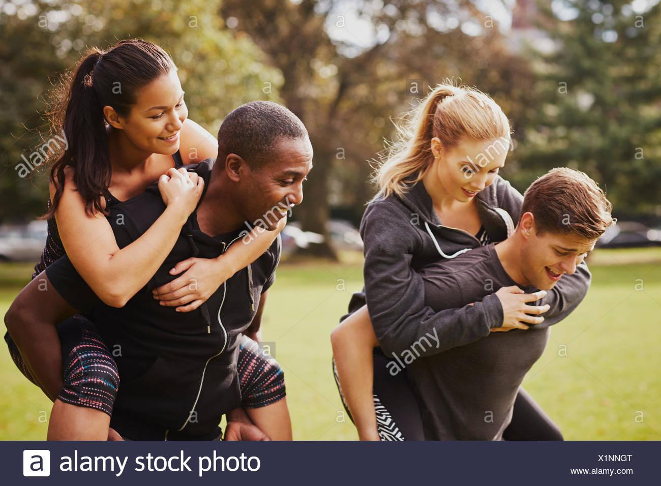 Männer und Frauen, die Spaß im Park, mit Huckepack-Rennen training Stockbild
