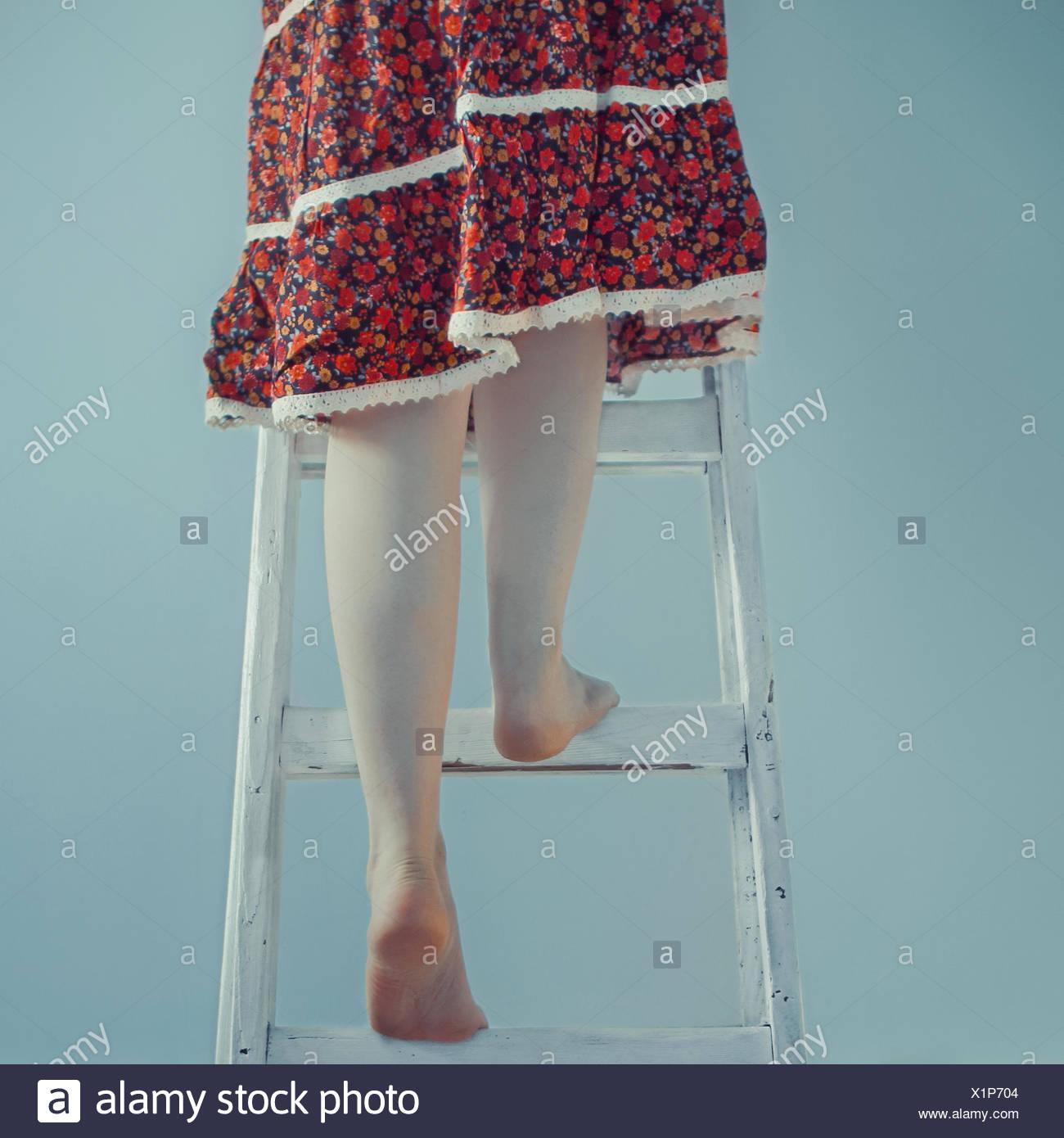 Frau auf eine Leiter klettern Stockbild