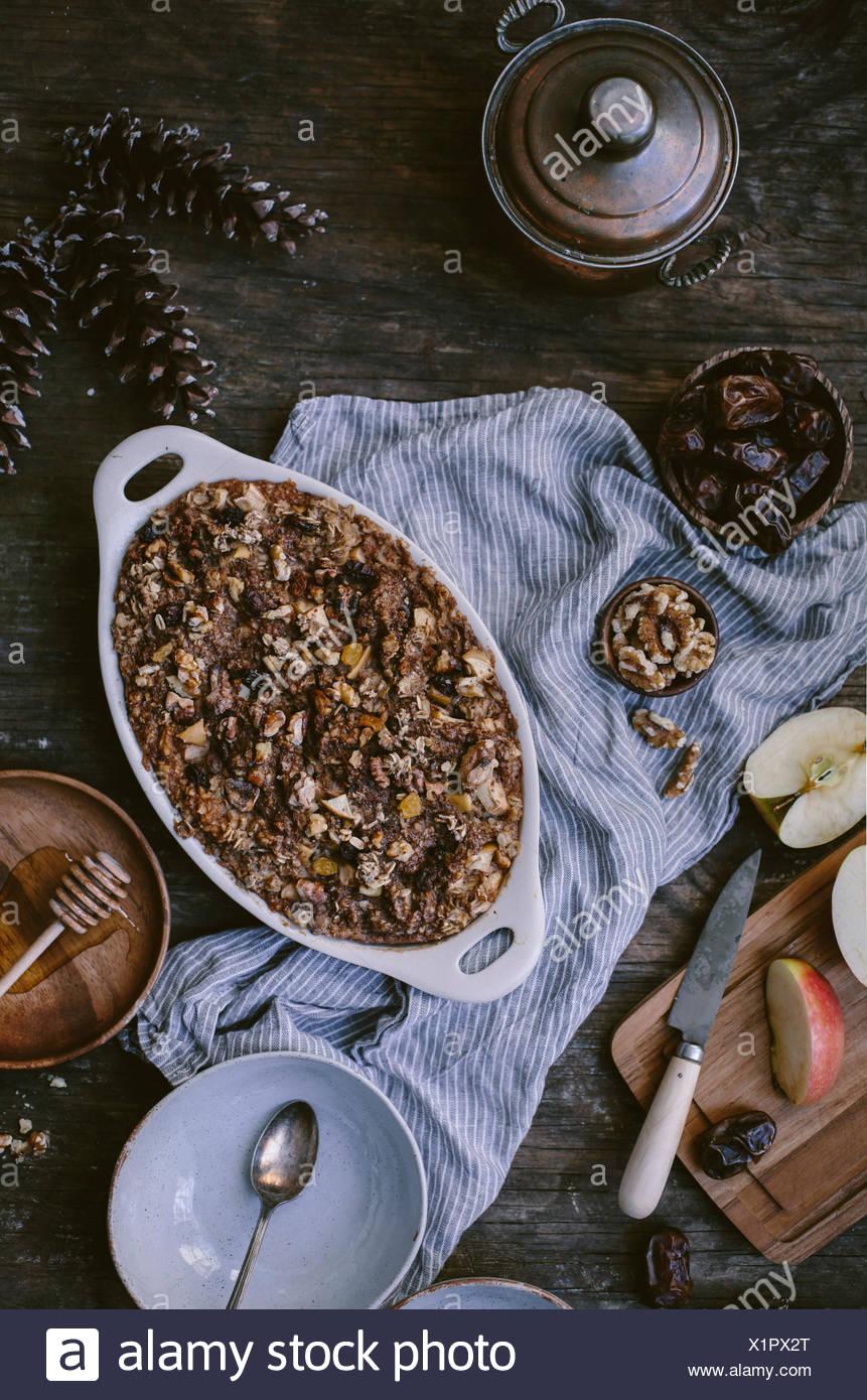 Gebackenes Haferflocken mit Datteln, Äpfel, Bananen und Walnuss ist frisch aus dem Ofen serviert und auf neu gewonnenem w angezeigt Stockbild